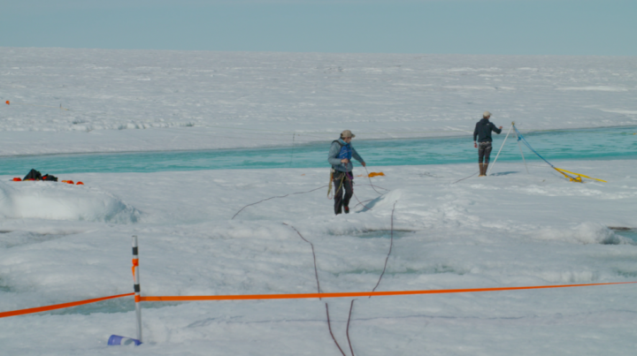 Two researchers with Smith's team move a sonar-like instrument back and forth across the waters of a melt water river on Greenland's ice sheet, to measure the depth and speed of the waters. Credits: NASA's Goddard Space Flight Center/Jefferson Beck