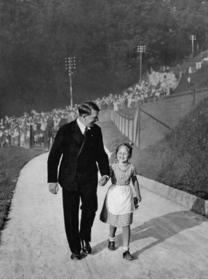 """Adolf Hitler escorts a young girl, Rosa Bernile Nienau, to his house on the Obersalzberg. Photograph from Heinrich Hoffman's """"Youth Around Hitler."""" Image credit: Heinrich Hoffman, Bavarian State Library"""