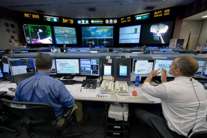 Expedition 43 Flight Director Gary Horlacher (left) and Capcom David Saint-Jacques (right) in Mission Control Houston at the Johnson Space Center during the release of the SpaceX Dragon cargo vehicle. CAPCOM personnel communicate regularly with crew members and participated in the investigation. Credits: NASA