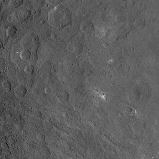 This image of Ceres, taken by NASA's Dawn spacecraft, features a large, steep-sided mountain and several intriguing bright spots. The mountain's height is estimated to be about 4 miles (6 kilometers), which is a revision of the previous estimate of 3 miles (5 kilometers). Credits: NASA/JPL-Caltech/UCLA/MPS/DLR/IDA