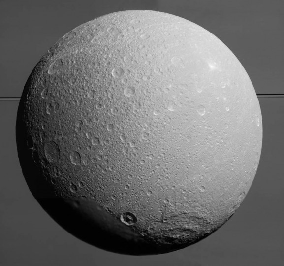 This view from NASA's Cassini spacecraft looks toward Saturn's icy moon Dione, with giant Saturn and its rings in the background, just prior to the mission's final close approach to the moon on August 17, 2015. Credits: NASA/JPL-Caltech/Space Science Institute
