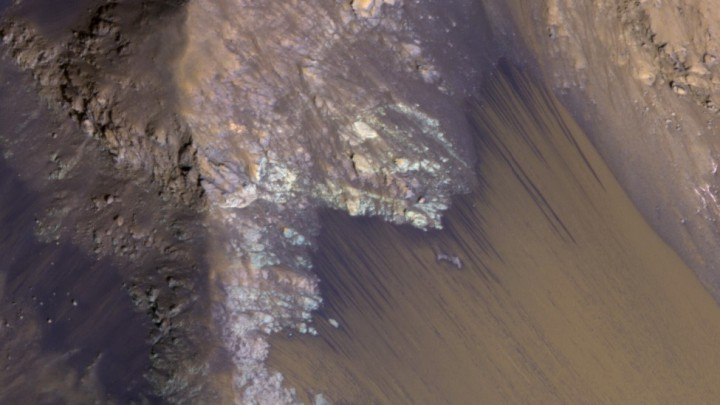 Among the many discoveries by NASA's Mars Reconnaissance Orbiter since the mission was launched on Aug. 12, 2005, are seasonal flows on some steep slopes, possibly shallow seeps of salty water. This July 21, 2015, image from the orbiter's HiRISE camera shows examples within Mars' Valles Marineris. Image credit: NASA/JPL-Caltech/Univ. of Arizona