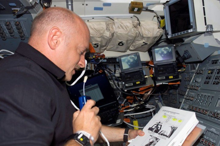 STS-121 Pilot Mark Kelly, talks with mission control as he reads a checklist on the aft flight deck (AFD) of the orbiter. Communication delays between Mission Control and crew members during the Comm Delay Assessment that took place during a recent International Space Station increment posed challenges for crew members. Credits: Mark Kelly