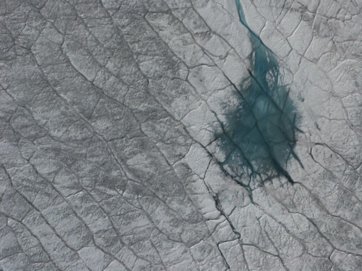 A grayish turquoise melt pond on the Greenland ice sheet, as seen from the air. Credits: NASA