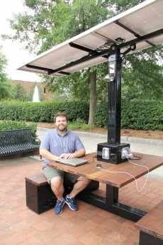Brian Holcombe, a senior majoring in anthropology, helped install a new solar-powered charging station near Herty Field that lets visiotors charge electronic devices like laptops and smartphones.