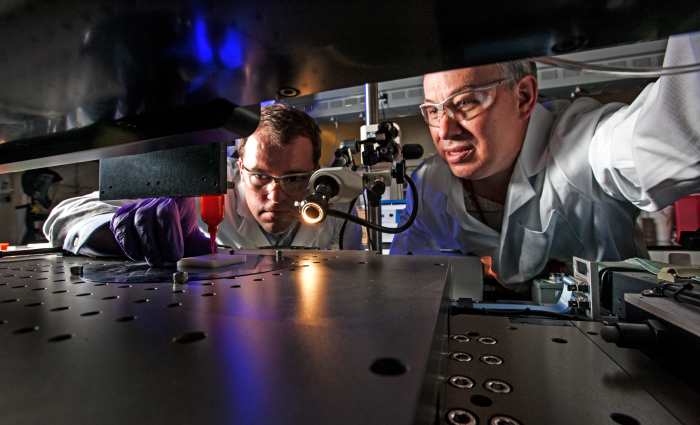 "Lawrence Livermore National Laboratory (LLNL) engineers Eric Duoss (left) and Tom Wilson use an additive manufacturing process called direct ink writing to develop an engineered ""foam"" cushion. Photo by George Kitrinos/LLNL"