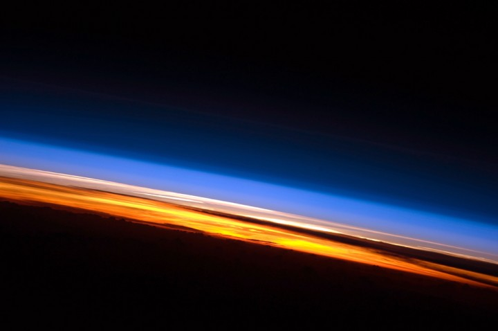 In this photo of sunset from the International Space Station, three atmospheric layers are distinctly visible. The troposphere glows orange, the stratosphere appears pale pink, and upper layers of the atmosphere are lighter blue. Credits: NASA