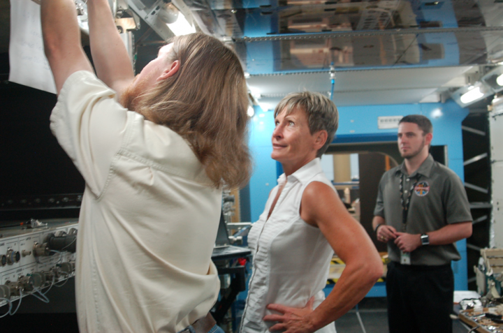 Thomas Sheene and Jason Kish instruct astronaut Peggy Whitson on science racks in a space station mock-up. Credits: NASA