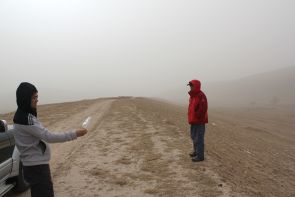 During a windstorm on China's Loess Plateau, geoscientist Fulong Cai uses a plastic bag as a wind sock to show that the wind blows parallel to the linear ridge he and Wang Zhao are standing on. Roads in this area run along the ridges. Image credit: Paul Kapp/ UA Department of Geosciences