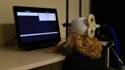 University of Washington postdoctoral student Caitlin Hudac wears a cap that uses transcranial magnetic stimulation (TMG) to deliver brain signals from the other participant. Image credit: University of Washington