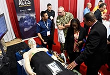 Eugene Daniels, right, a contractor with the Office of Naval Research (ONR), explains the Autonomous Critical Care System (ACCS) to attendees during the Modern Day Marine Expo at Marine Corps Base, Quantico, Va. The ACCS is designed to help physicians monitor patients' vital signs, administer fluids and maintain their stability in transport. (U.S. Navy photo by John F. Williams/Released)