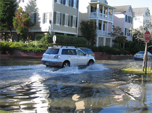 A car splashes through a flooded Charleston neighborhood. Nuisance flooding causes public inconveniences such as frequent road closures, overwhelmed storm water systems, and compromised infrastructure. Image credit: NOAA