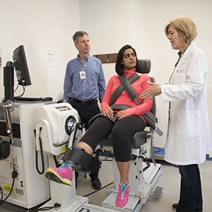 Cardiology fellow Nishtha Sodhi, MD, (center) demonstrates equipment used to measure muscle power. A study co-authored by Andrew Coggan, PhD, (left) and Linda Peterson, MD, showed that drinking concentrated beet juice boosts muscle power in patients with heart failure. Image credit: Robert Boston