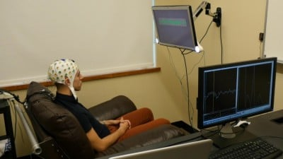 University of Washington graduate student Jose Ceballos wears an electroencephalography (EEG) cap that records brain activity and sends a response to a second participant over the Internet. Image credit: University of Washington