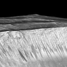 Dark narrow streaks called recurring slope lineae flowing out of the walls of Garni Crater on Mars. The streaks are up to a few hundred meters in length. Photo is color enhanced. Image credit: NASA/JPL/University of Arizona.