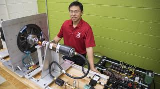 Jie Cheng, doctoral student in electrical engineering, stands next to the partial prototype of a wind turbine system that research suggests could yield 8.5 percent more electricity than conventional counterparts. Image credit: Troy Fedderson/University Communications