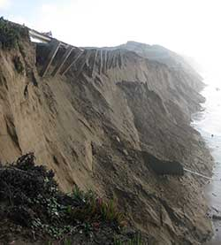 Severe bluff erosion, along the southern end of Ocean Beach, San Francisco, California, including damage to the guard rail of the Great Highway (Calif. Hwy.1). The severe winter erosion led to lane closures of the highway and an emergency, $5 million revetment along the base of this bluff. This storm damage occurred during the 2009-2010 El Niño, which, on average, eroded the shoreline 55 meters that winter.