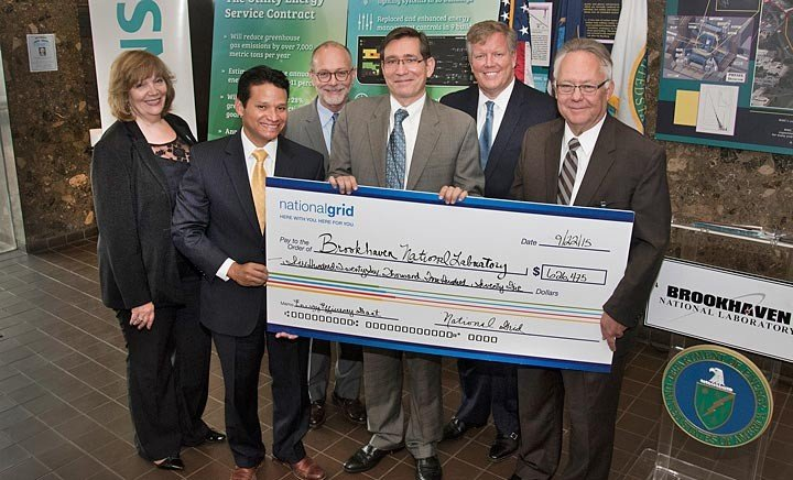 Mike Ruiz, National Grid's Director of Community and Customer Management (second from left), presents a $626,475 rebate/grant check to Brookhaven Lab Director Doon Gibbs (far right) and U.S. Department of Energy (DOE) Brookhaven Site Office (BHSO) Business Management Division Director Evelyn Landini (far left). The check reflects new rebates and grants made possible by the UESC energy-efficiency upgrades at the Lab. Also pictured (from left) are John Carter, BHSO Communications Director; John Shonder, Director, Sustainability Performance Office, DOE, and Dave Hopping, president of Siemens' North American-based Building Technologies Division.