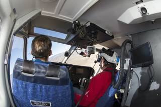Dave Fedors wears the Fused Reality helmet while flying the Gippsland GA-8 Airvan. NTPS instructor Bryan Olson, in the left seat, served as safety pilot. Credits: NASA Photo / Carla Thomas