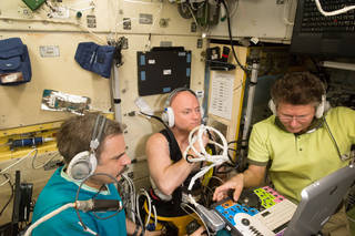 NASA astronaut Scott Kelly, center, takes medical measurements as part of the Fluid Shifts investigations along with Russian cosmonauts Mikhail Kornienko, left, and Gennady Padalka. Fluid Shifts measures how much fluid shifts from the lower body to the upper body, and determines the impact these shifts have on fluid pressure in the head, changes in vision and eye structures. Credits: NASA