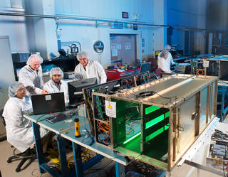 A team of scientists and engineers test the components of Saffire I (background) and Saffire II (foreground) Credits: NASA