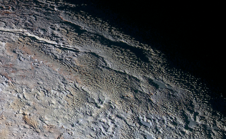 This color image of Pluto taken by NASA's New Horizons spacecraft shows rounded and bizarrely textured mountains, informally named the Tartarus Dorsa, that rise up along Pluto's terminator and show intricate but puzzling patterns of blue-gray ridges and reddish material in between. This view, roughly 330 miles (530 kilometers) across, combines blue, red and infrared images taken by the Ralph/Multispectral Visual Imaging Camera (MVIC) on July 14, 2015, and resolves details and colors on scales as small as 0.8 miles (1.3 kilometers). Credits: NASA/JHUAPL/SWRI