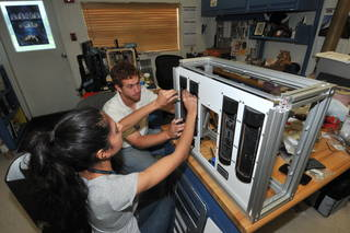 Experimental equipment mechanical design engineer Prital Thakrar (left) and University of Florida student Bradley Shea reassemble the E-MIST hardware after avionics testing in the Prototype Development Laboratory at Kennedy Space Center. Credits: NASA