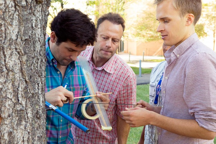 Instructors Ulf Büntgen of the Swiss Federal Research Institute (left) and Jürg Luterbacher of Justus Liebig University in Germany (center) work with Georgetown University Ph.D. student Jackson Perry to remove and examine a tree core on the Princeton campus. (Photos by Denise Applewhite, Princeton)