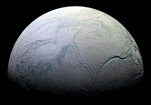 """Enceladus, showing the famous """"Tiger Stripes"""" feature – a series of fractures bound on either side by colorful ice. Credit: NASA/JPL/Space Science Institute"""
