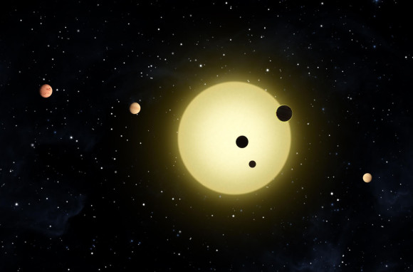 Kepler-11, a sun-like star orbited by six planets. At times, two or more planets pass in front of the star at once, as shown in this artist's conception of a simultaneous transit of three planets observed by the Kepler spacecraft on Aug. 26, 2010. During each pass or transit, the star's light fades in a periodic way.  Credit: NASA/Tim Pyle