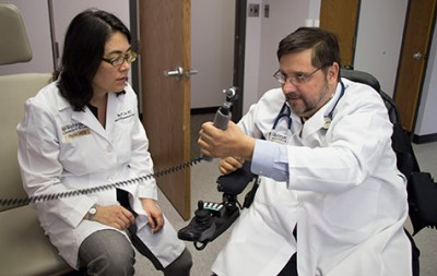 Washington University physician Michael Bavlsik, MD, shows surgeon Ida Fox, MD, how he can now grip an otoscope, which he uses in his practice. He is one of nine quadriplegic patients who regained some hand and arm movement after nerve-transfer surgery, a procedure pioneered at Washington University School of Medicine. Fox, an assistant professor of surgery, operated on Bavlsik. Image credit: E. Holland Durando