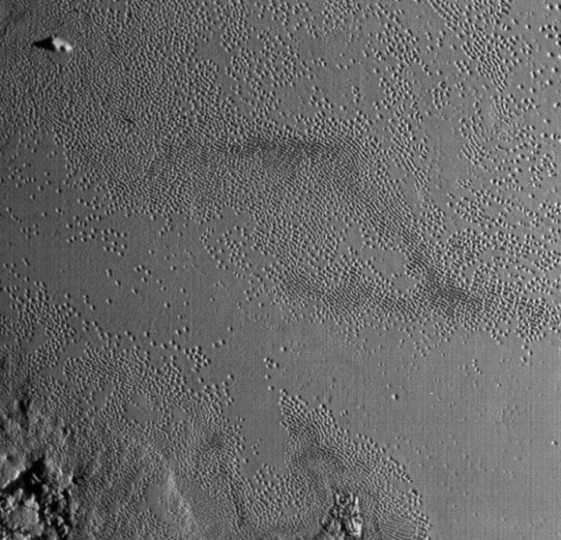 "Life's definitely the pits on Pluto's Tombaugh Regio. This photo shows the fainter ""ghost"" pits well. Is ice filling them in or are we seeing the beginning of a pit's formation? Credit: NASA/JHUAPL/SwRI"