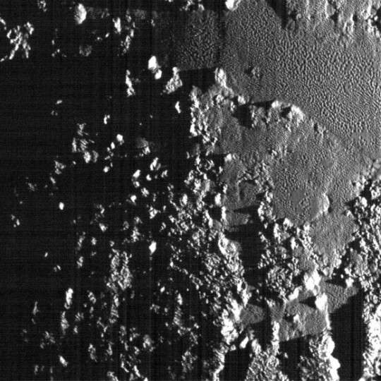 Now that's what I call getting a photo in low light. Sunlight scrapes across rugged mountains as well as highlight the ubiquitous pitted terrain. Credit: NASA/JHUAPL/SwRI