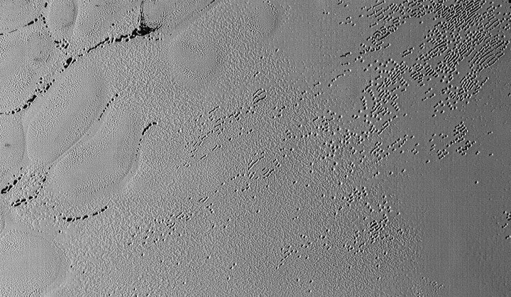 Rows of small pits pockmark the ice in Sputnik Planum on Pluto in this latest photo returned by NASA's New Horizons spacecraft shortly before closest approach to Pluto on July 14, 2015. Could these divots be caused by sublimating nitrogen ice? It resolves details as small as 270 yards (250 meters) and the scene is about 130 miles (210 km) across. Credits: NASA/JHUAPL/SwRI