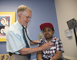 Robert Strunk, MD, examines LeBron Reed, a patient with asthma. Strunk, of Washington University School of Medicine in St. Louis, led a study showing the importance of children with asthma maintaining healthy weight as they grow into young adults. Image credit: Robert Boston