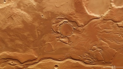 In this image of the Mangala Valles and Minio Vallis region- about 200 kilometres from its outflow on the border of the northern Martian lowlands- the subtle variations in colour reveal how masses of water have at different times transported sediments into this region and deposited them there. In this image, north is to the right. Image credit: HRSC