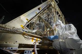 Contamination Control Engineer Alan Abeel conducts final inspections and places contamination foils before the start of the test. Credits: NASA/Chris Gunn