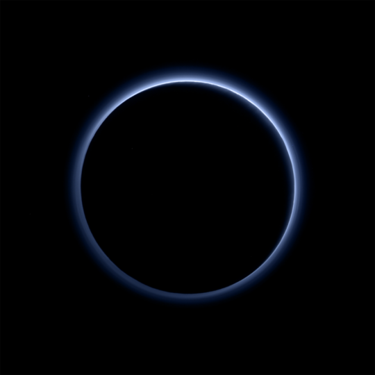 Pluto's Blue Sky: Pluto's haze layer shows its blue color in this picture taken by the New Horizons Ralph/Multispectral Visible Imaging Camera (MVIC). The high-altitude haze is thought to be similar in nature to that seen at Saturn's moon Titan. The source of both hazes likely involves sunlight-initiated chemical reactions of nitrogen and methane, leading to relatively small, soot-like particles (called tholins) that grow as they settle toward the surface. This image was generated by software that combines information from blue, red and near-infrared images to replicate the color a human eye would perceive as closely as possible. Credits: NASA/JHUAPL/SwRI