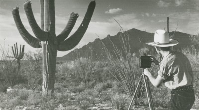 A young man photographs a saguaro cactus outside of the Herbert residence in Tucson. Image credit: Arizona Historical Society