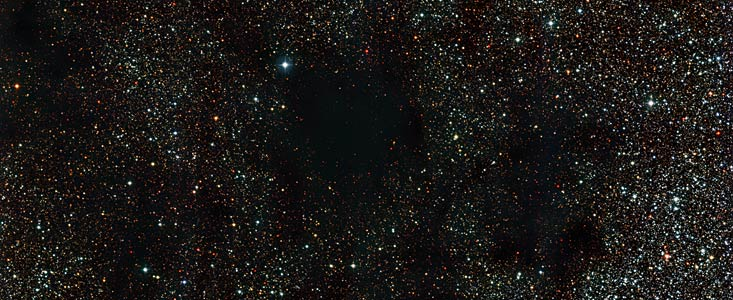 Dark smudges almost block out a rich star field in this new image captured by the Wide Field Imager camera, installed on the MPG/ESO 2.2-metre telescope at ESO's La Silla Observatory in Chile. The inky areas are small parts of a huge dark nebula known as the Coalsack, one of the most prominent objects of its kind visible to the unaided eye. Millions of years from now, chunks of the Coalsack will ignite, rather like its fossil fuel namesake, with the glow of many young stars.