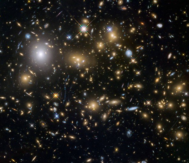 Hubble observations have taken advantage of gravitational lensing to reveal the largest sample of the faintest and earliest known galaxies in the universe. Some of these galaxies formed just 600 million years after the Big Bang. Credits: ESA/NASA