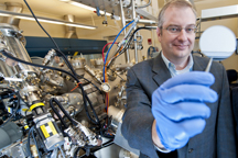 Purdue professor Michael Manfra holds a gallium-arsenide wafer as he stands next to the high-mobility gallium-arsenide molecular beam epitaxy system, or MBE, at the Birck Nanotechnology Center. Manfra leads a team of Purdue researchers that create ultrapure semiconductor heterostructures to study electrons in correlated states. Image credit: Purdue University photo/Andrew Hancock