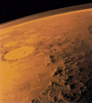 In this image taken by the Viking 1 orbiter in June 1976, the translucent layer above Mars' dusty red surface is its atmosphere. Compared to Earth's atmosphere, the thin Martian atmosphere is a less powerful shield against quick-moving, energetic particles that pelt in from all directions – which means astronauts on Mars will need protection from this harsh radiation environment