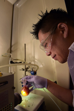 Sandia National Laboratories post-doctoral fellow Stan Chou demonstrates the reaction of more efficiently catalyzing hydrogen. In this simulation, the color is from dye excited by light and generating electrons for the catalyst molybdenum disulfide to evolve hydrogen. (Photo by Randy Montoya) Click on the thumbnail for a high-resolution image.