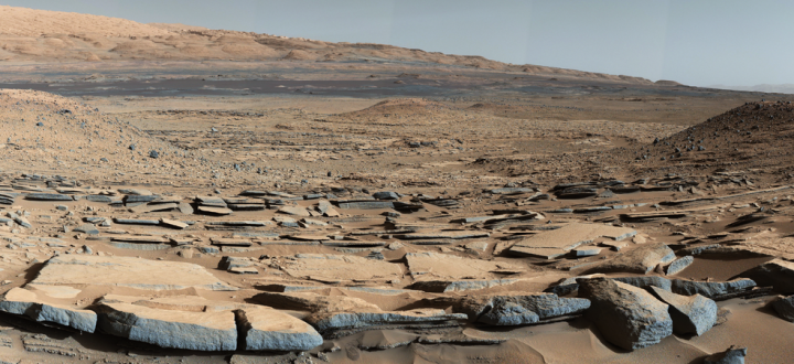 """A view from the """"Kimberley"""" formation on Mars taken by NASA's Curiosity rover. The strata in the foreground dip towards the base of Mount Sharp, indicating flow of water toward a basin that existed before the larger bulk of the mountain formed. Credits: NASA/JPL-Caltech/MSSS"""