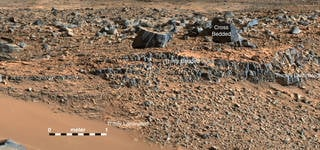 """An image taken at the """"Hidden Valley"""" site, en-route to Mount Sharp, by NASA's Curiosity rover. A variety of mudstone strata in the area indicate a lakebed deposit, with river- and stream-related deposits nearby. Credits: NASA/JPL-Caltech/MSSS"""