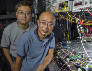 Guan Yang (right) and his research associate, Wei Lu, pose in front of the lasercom breadboard they created to demonstrate high data-rate download and uplink speeds as well as highly precise distance and speed measurements all from the same, relatively small package. Credits: NASA/W. Hrybyk