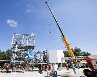 Workers at a construction yard lift and connect the White Room to the end of the Crew Access Arm that will be installed next year on the Crew Access Tower.