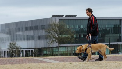 Sean Mealin and Simba, using a traditional guide dog harness and handle. Image credit: NC State University.