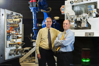Goddard engineer Michael Kienlen, who is studying servicing beyond low-Earth orbit, and Benjamin Reed, deputy project manager of Goddard's Satellite Servicing Capabilities Office, stand in front of a mockup of the Robotic Refueling Mission now deployed on the International Space Station. Credits: NASA/C. Gunn